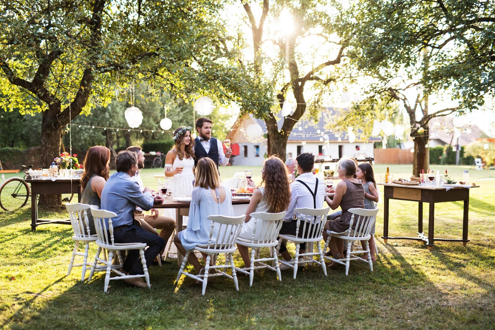 Bride and groom in a beautiful outdoor wedding around the table with their guests