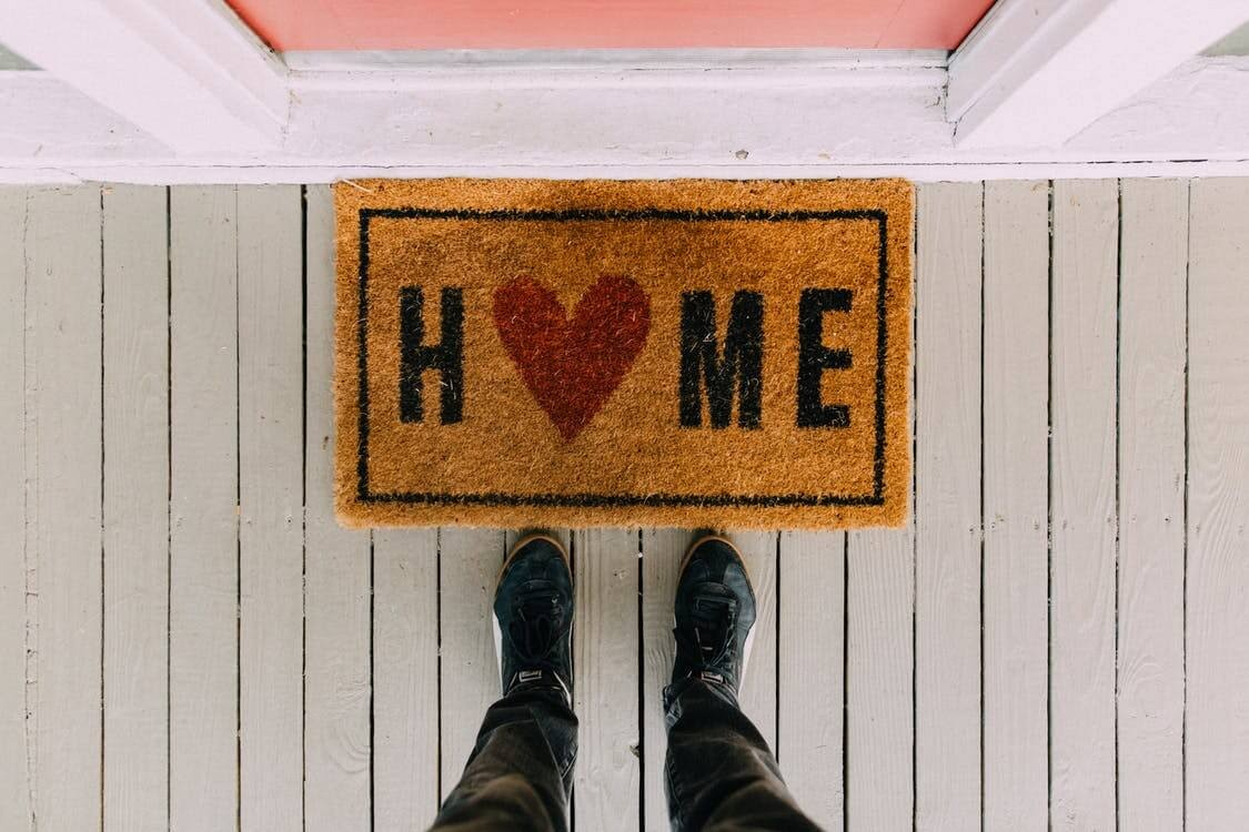 """Home mat in front of the door, with a heart for the """"o"""""""