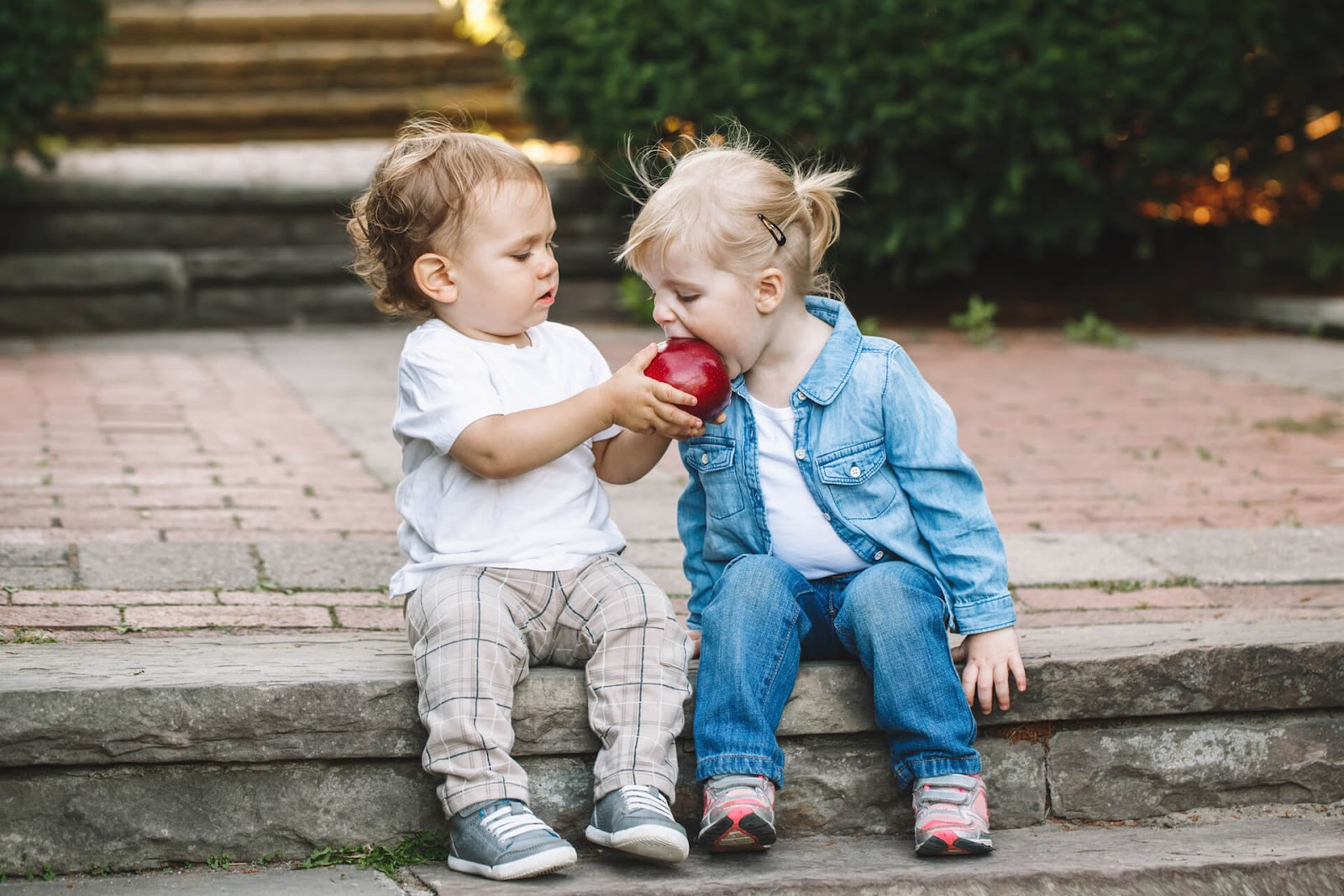 Toddler boy sharing his apple with a girl