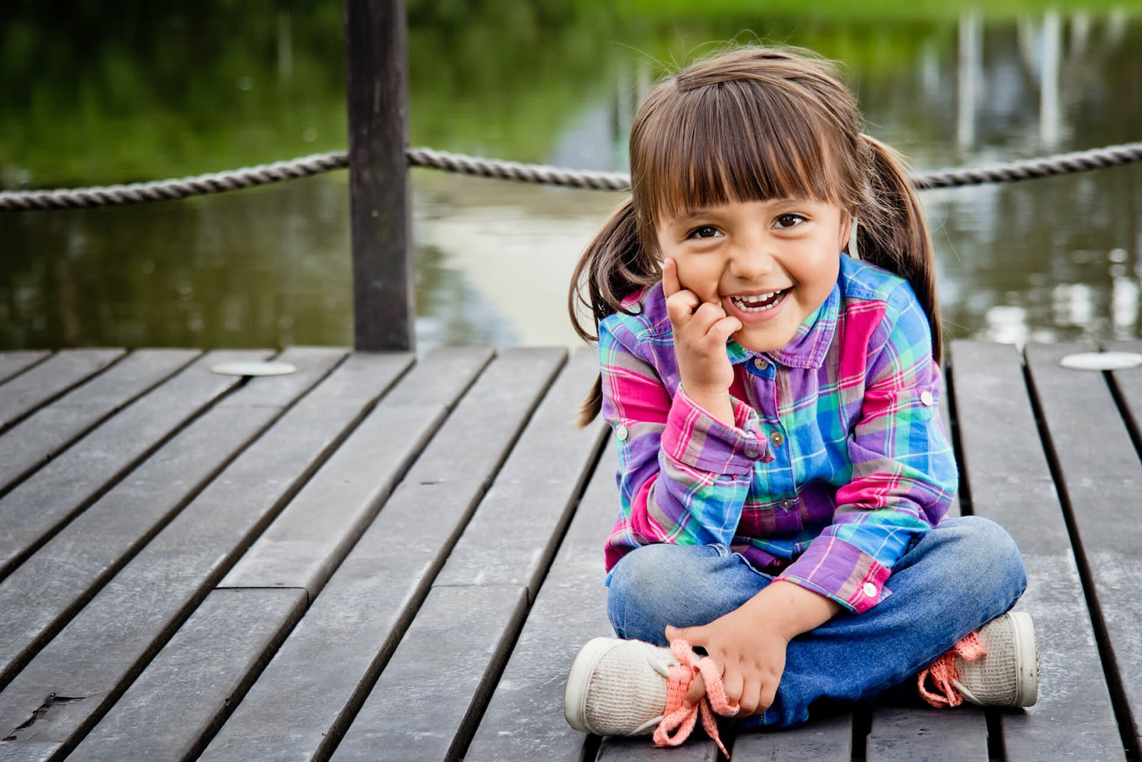 Four year old girl smiling at thee camera with a lake in the background