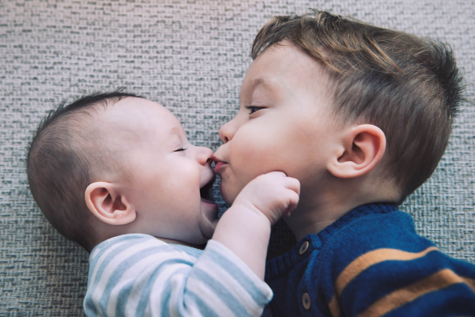 Young boy kissing his baby brother