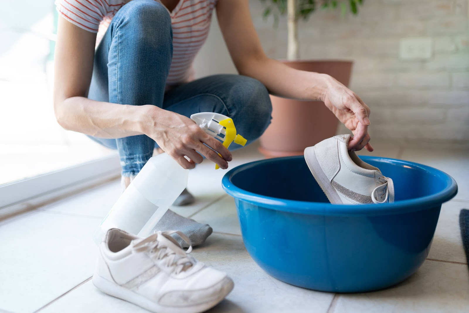 Woman spraying her shoes in a big, blue bucket