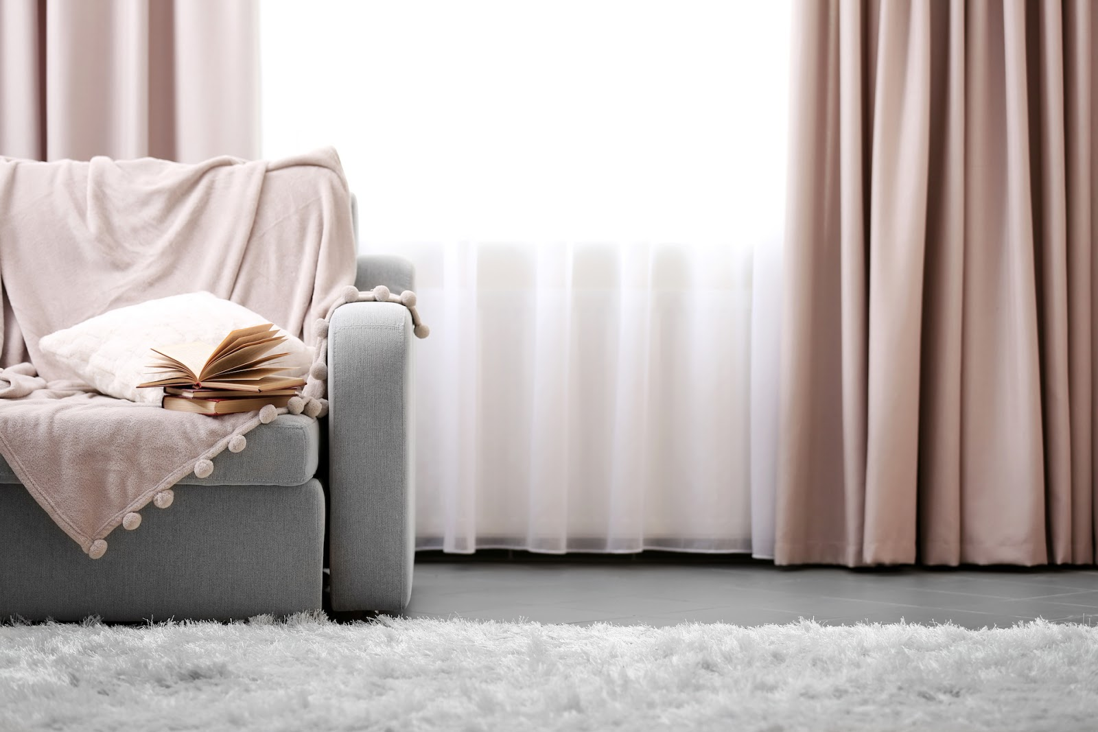 Dusty rose curtains with grey couch and pink blanket draped over itv