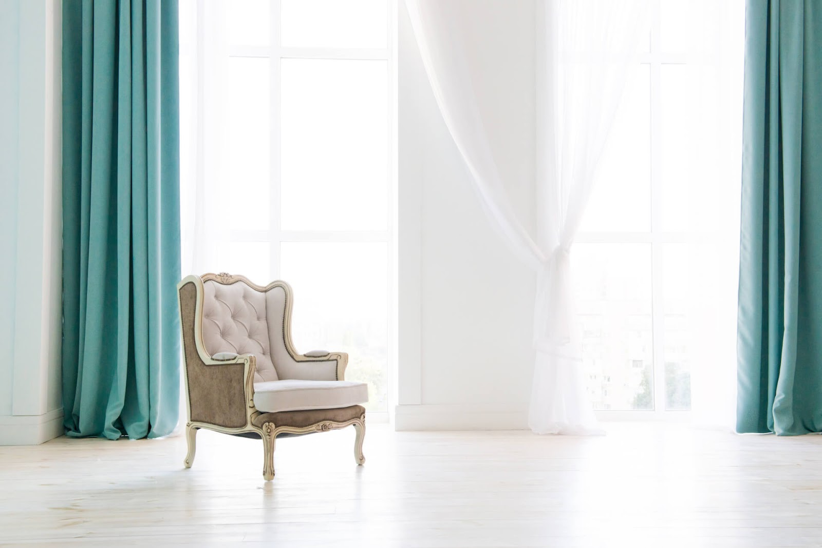 White wingback chair in white room with teal, floor-to-ceiling curtains