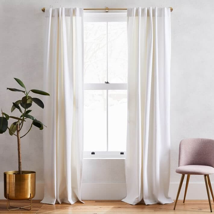 White curtains hanging over gold curtain rod