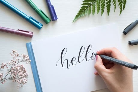 Woman writing hello on a paper
