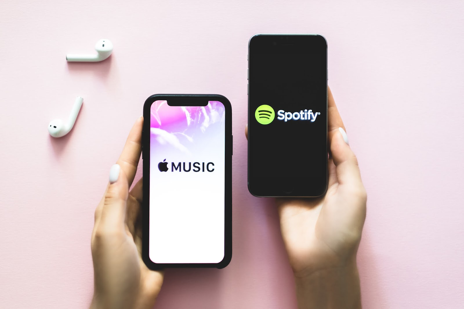 Woman holding a phone that says Apple music and one that says Spotify