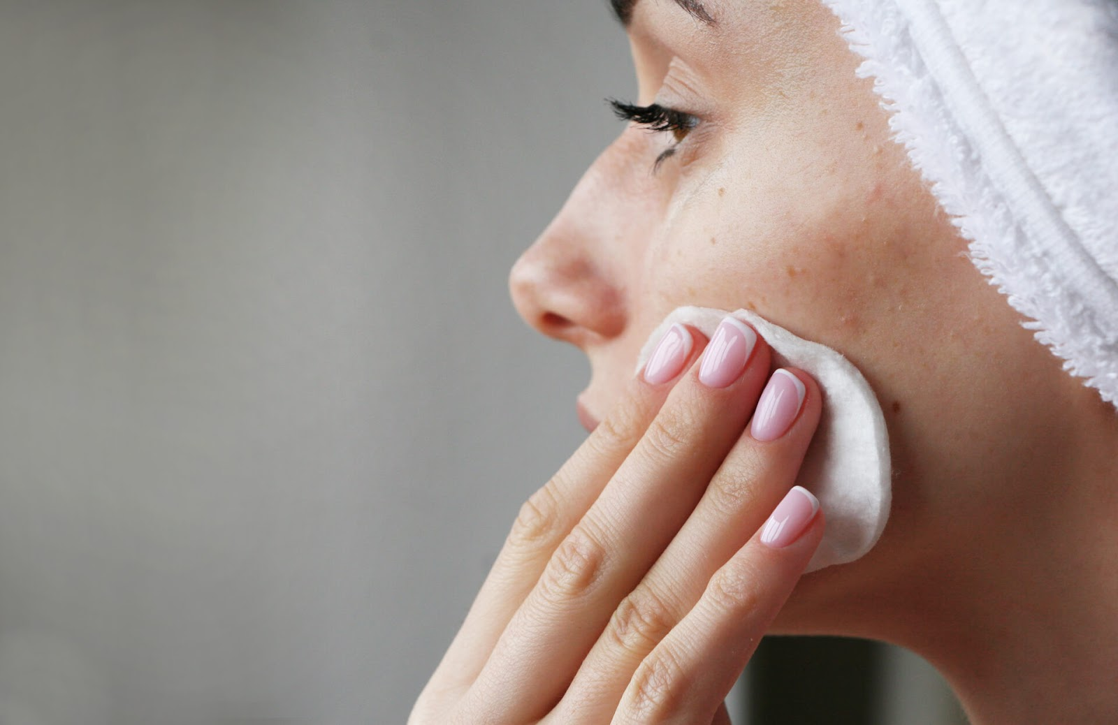 Woman rubbing her face with a cotton pad after a shower