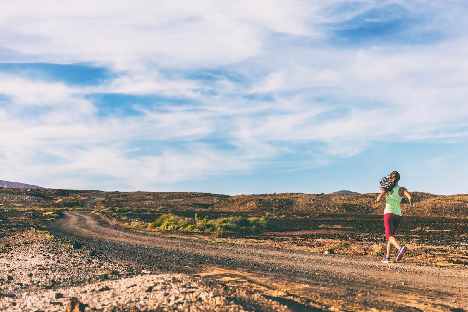 Woman jogging down a trail