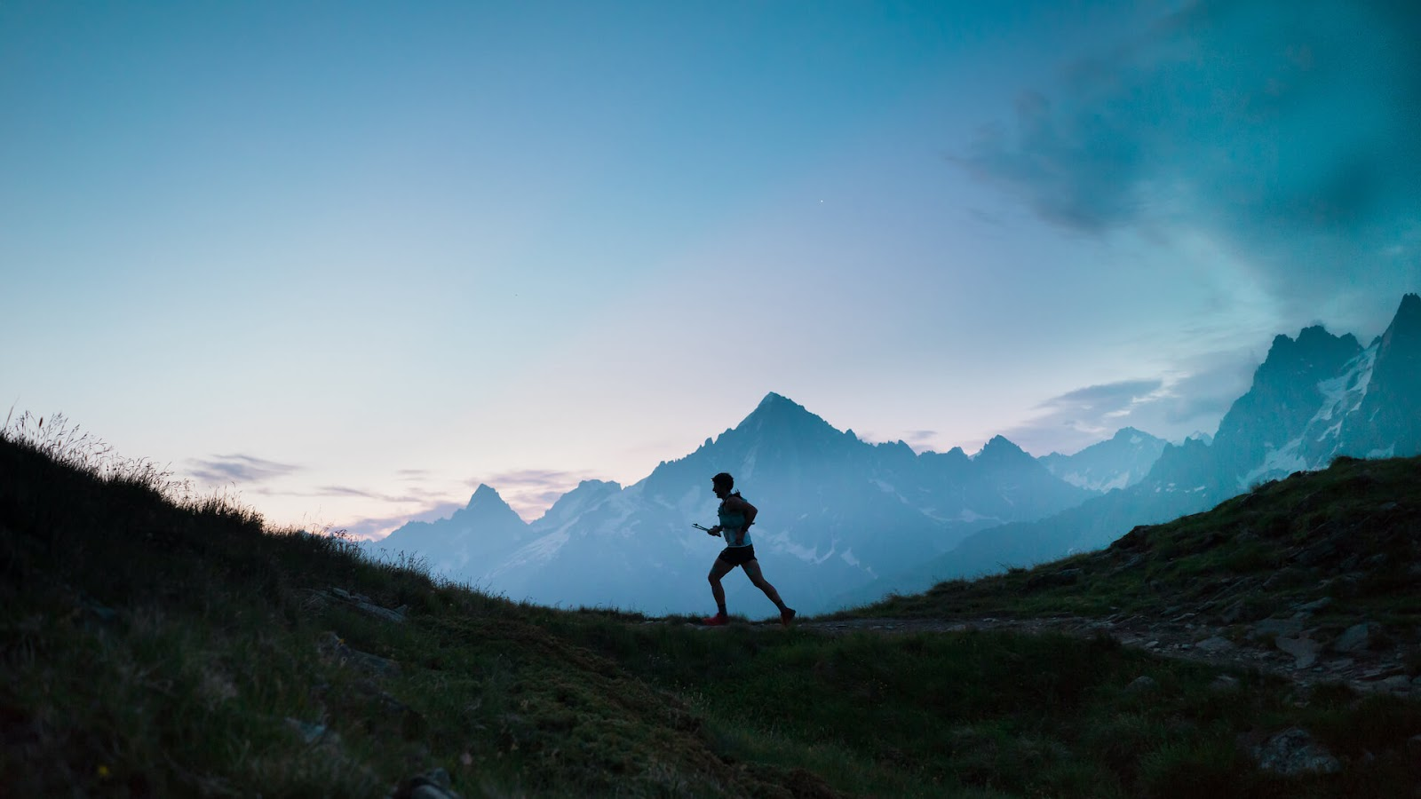 Man jogging on a trail with a mountain in the background