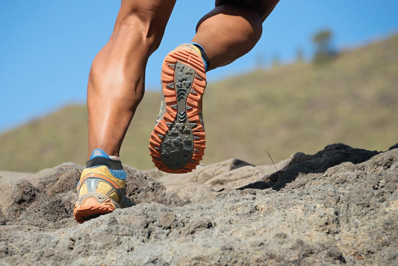 Close up of man's calves as he runs up rocks