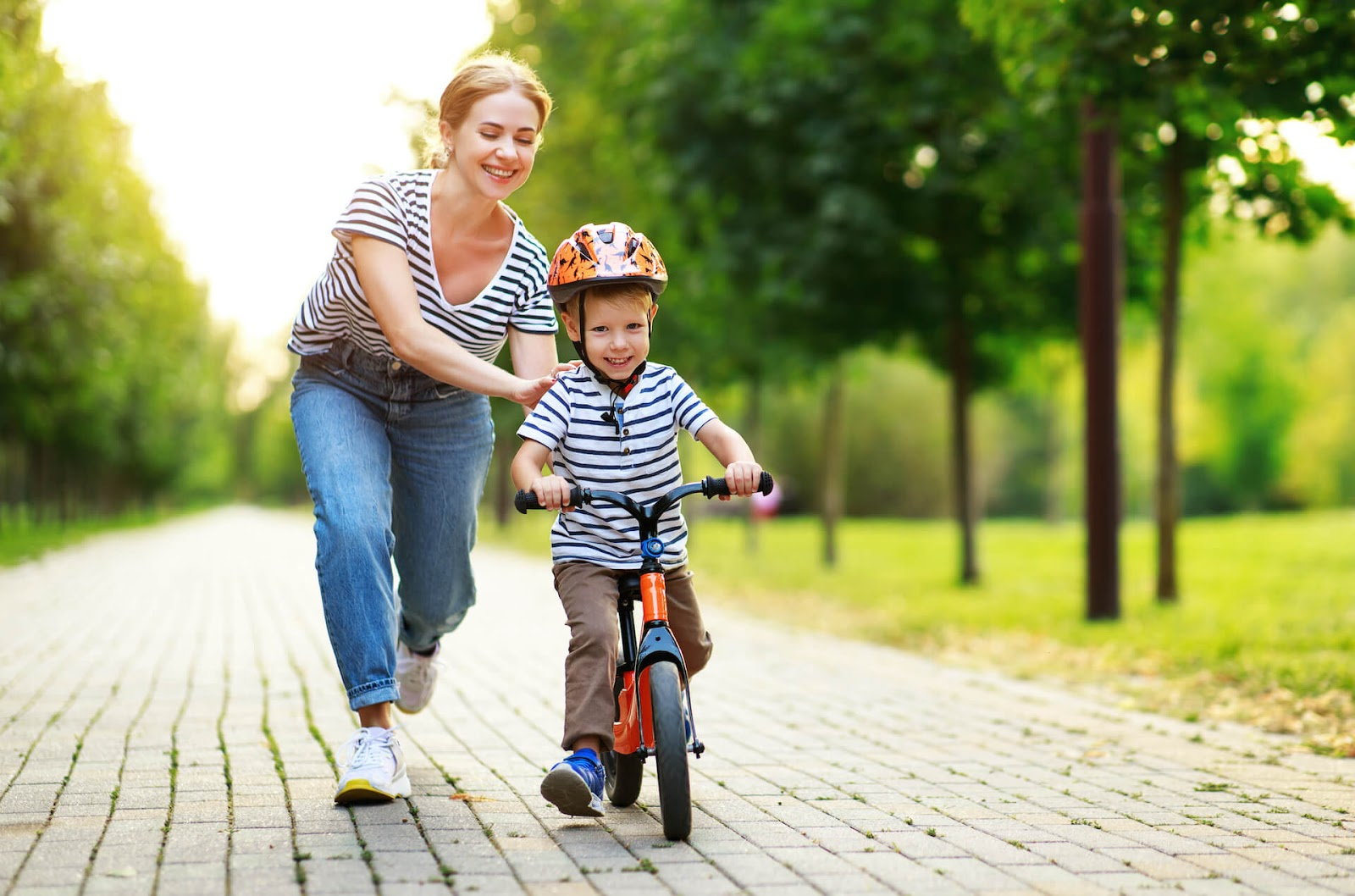 Mom teaching her son to ride a bike