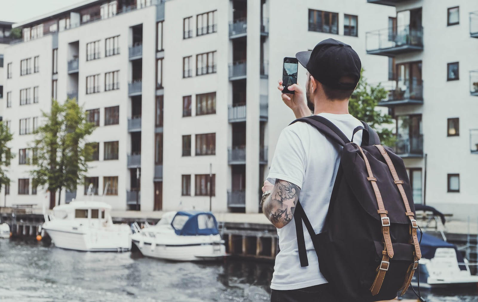 Man holding up phone to take a picture of some buildings
