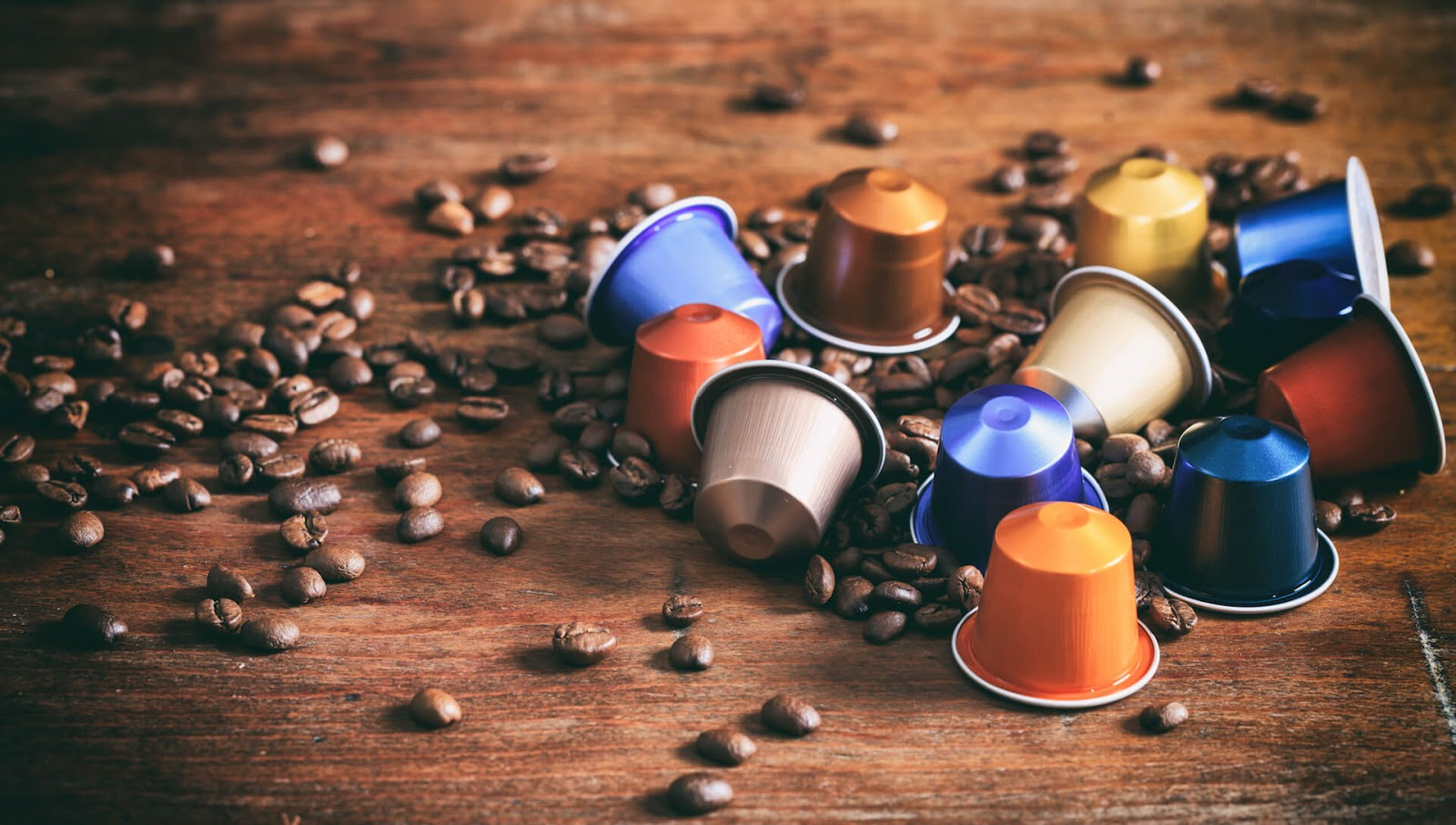 A pile of coffee pods next to some coffee beans