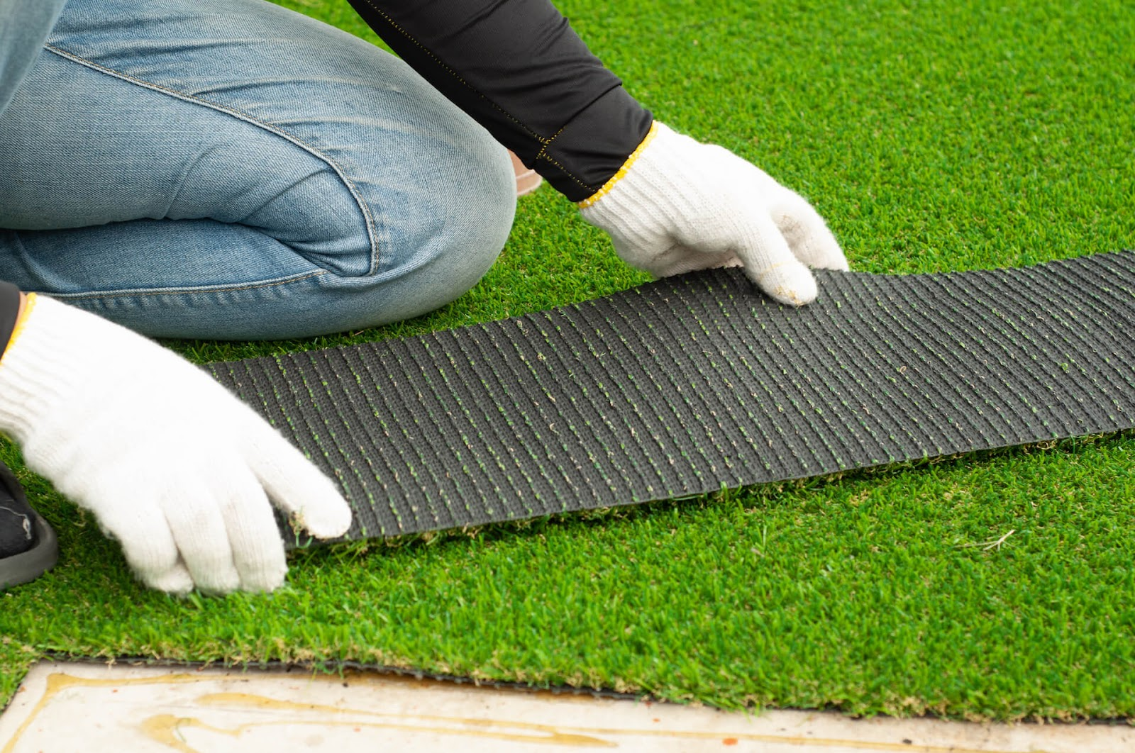 someone installing artificial grass