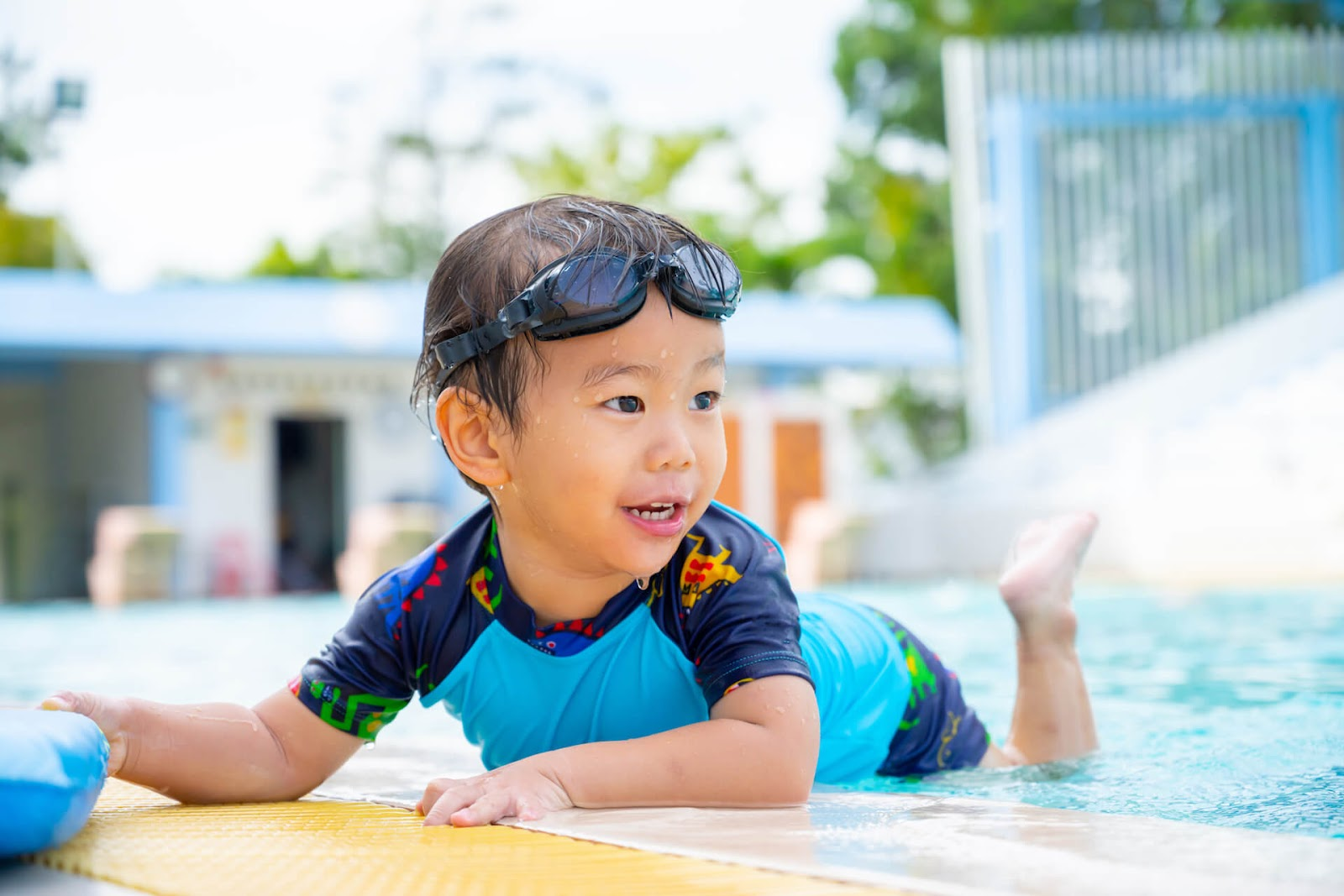 Young boy playing on his belly in the water with a swim shirt on
