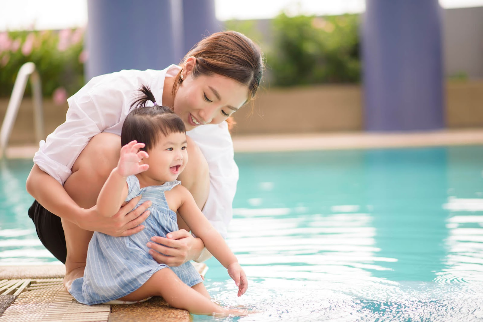 Mom introducing toddler daughter to pool