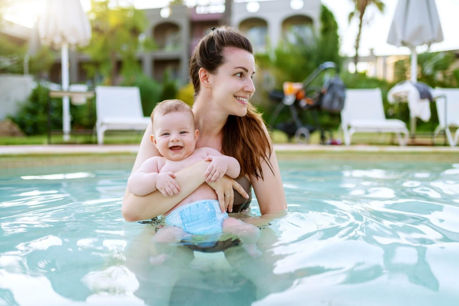 Mom holding young son with swim diapers in a swimming pool