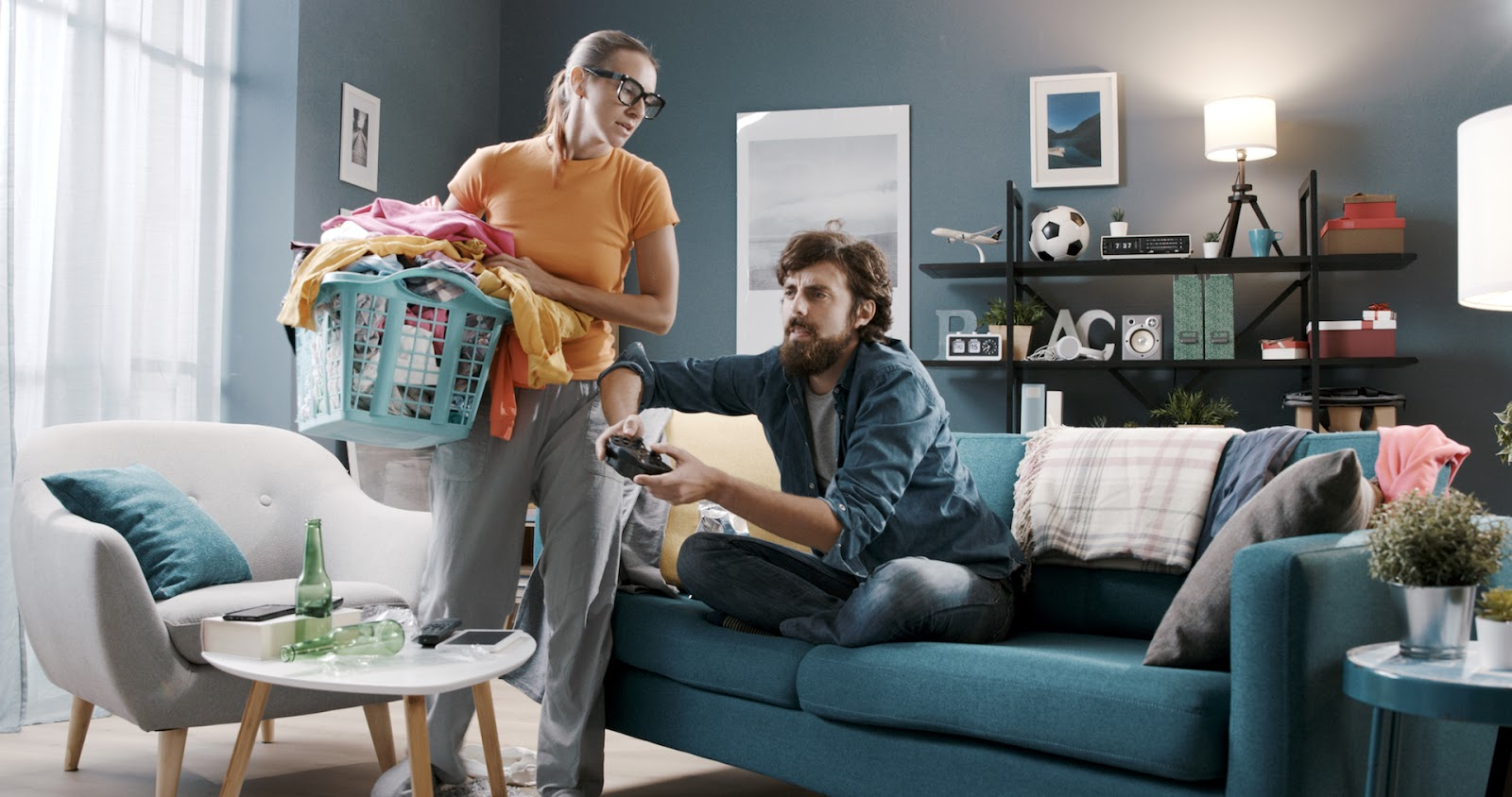 Frustrated woman doing laundry while her husband plays video games