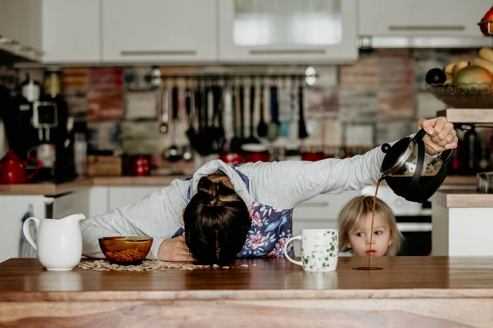 Tired mom pouring coffee on the counter as she misses her cup