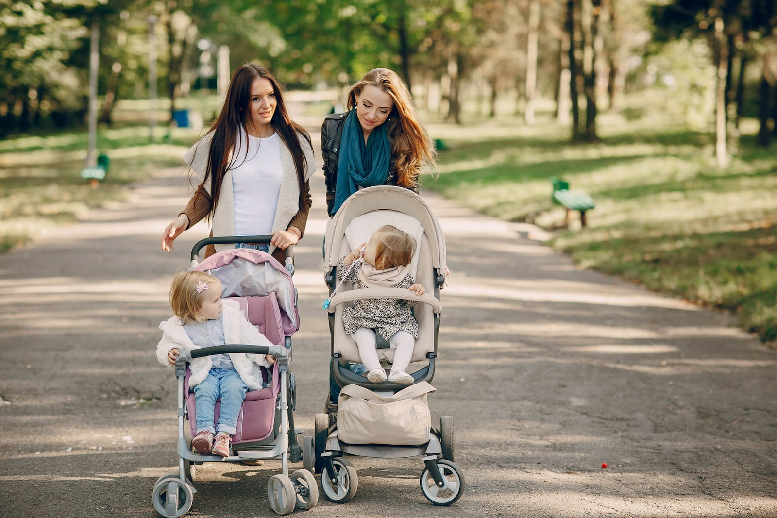 Two women pushing their strollers together