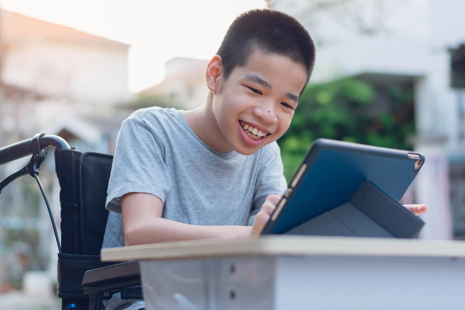 Young boy playing on his tablet from his wheelchair