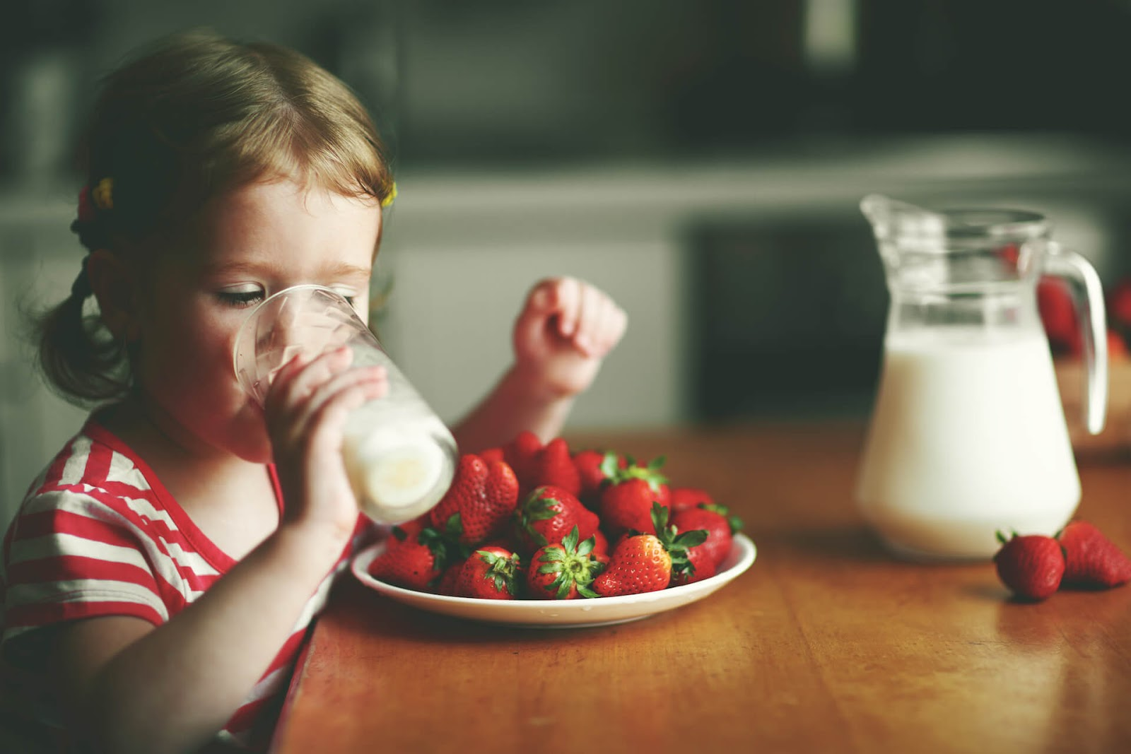 Young girl drinking pea milk with some strawberries nearby