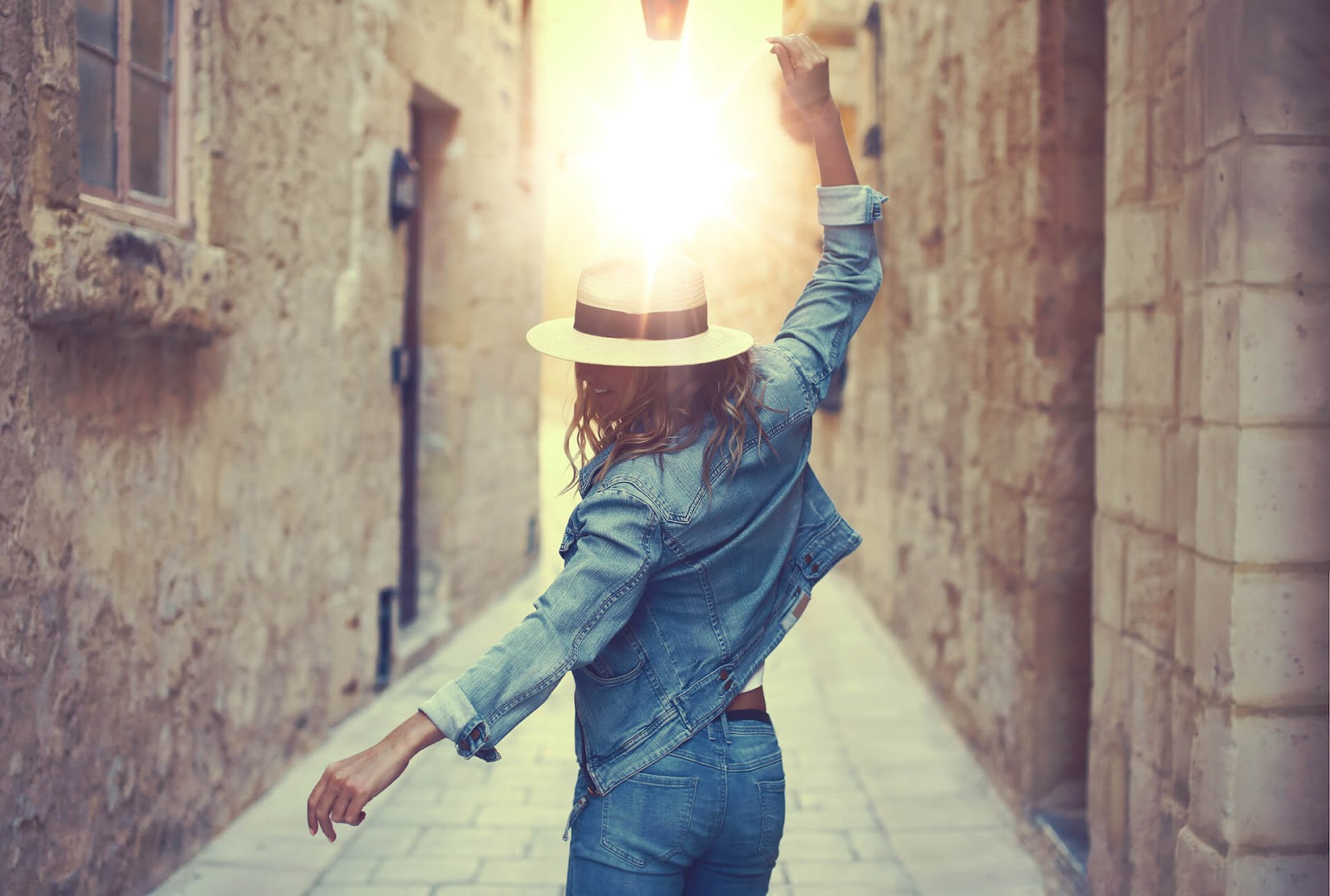 Woman dancing through a sun kissed alley