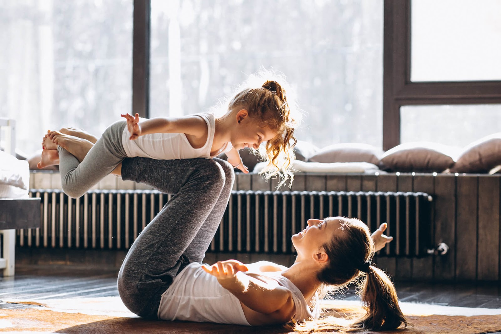 Woman doing chest opening yoga with her daughter