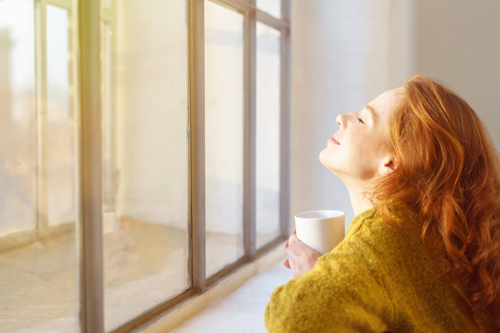 Woman soaking in the sun from her living room with a cup of
