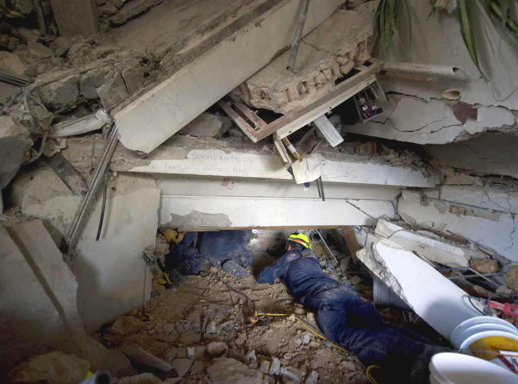 Photograph of rescuers attempting to free trapped guests within the rubble of Hotel Montana