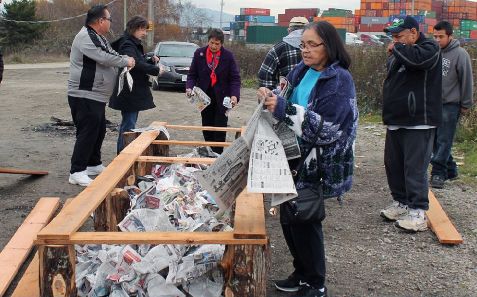 7 members of Stz'uminus tribe placing balled up newspaper in wooden structure.