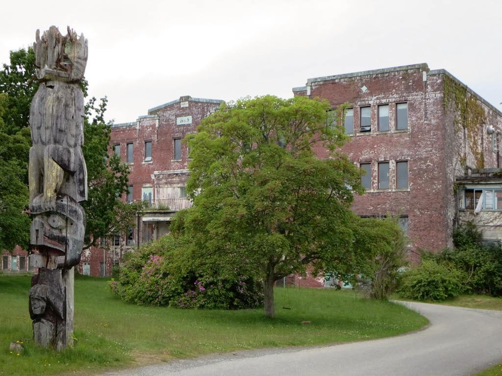 Derelict building with overgrown gardens and large wooden, Indian totem pole in foreground.