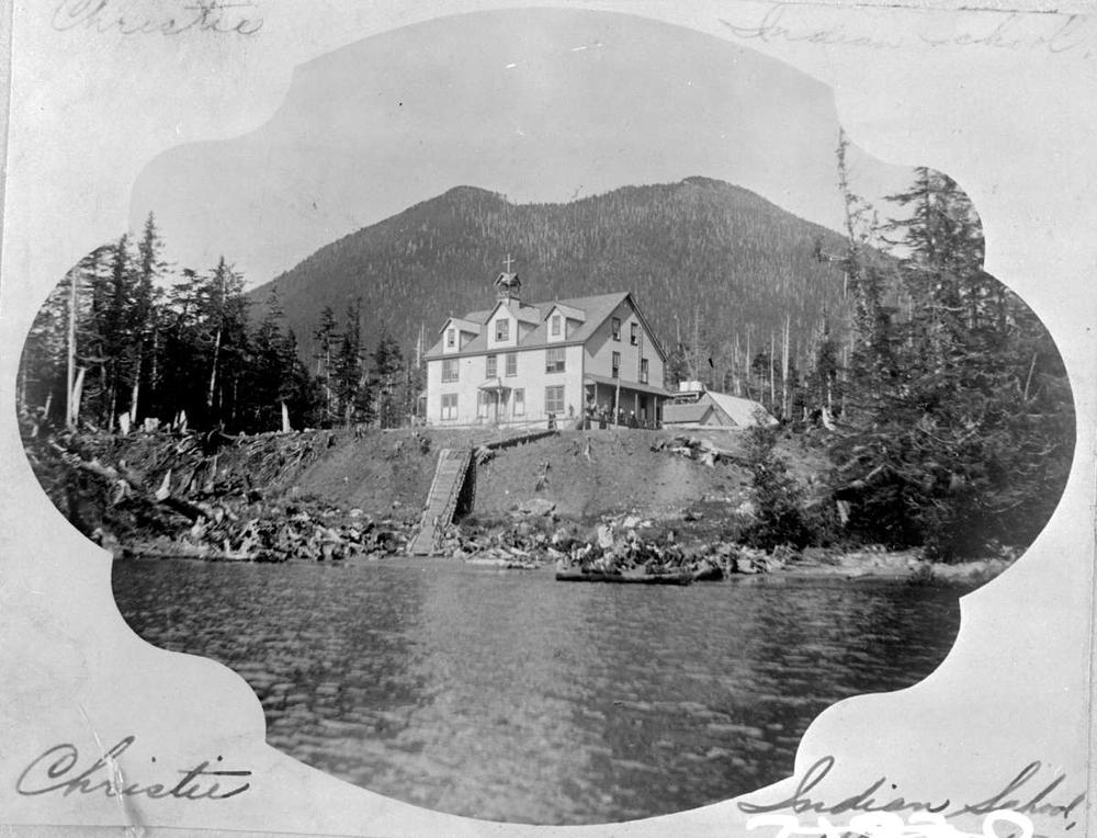 Black and white postcard with photograph of school sat atop raised land with water in foreground.