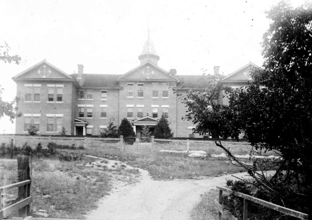 Black and white image of well maintained residential school with dirt road leading to fence and entrance.