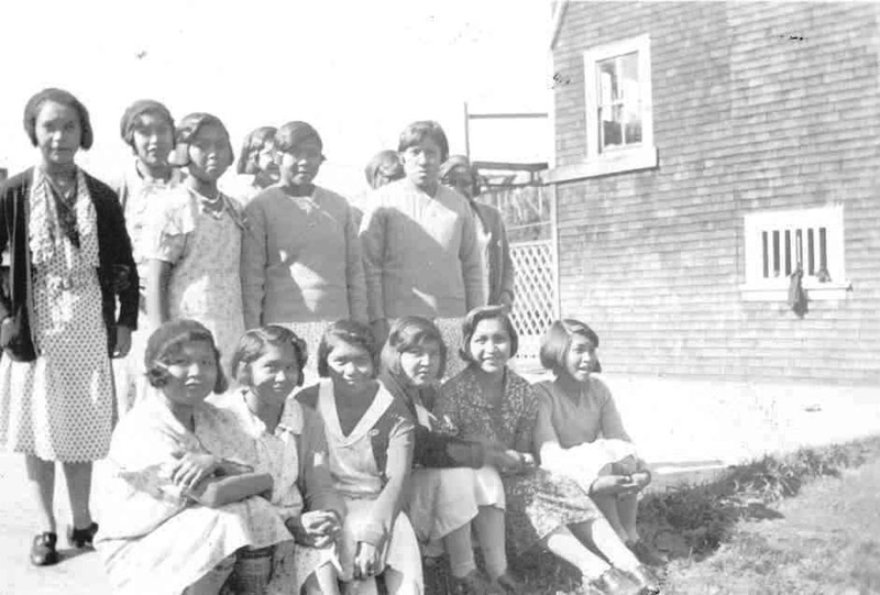 14 girls stood and sat in two lines in school yard.