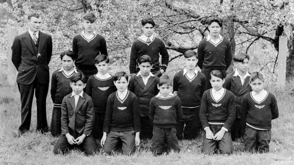 Teach and 13 pupils posed in 3 lines in field with trees behind.