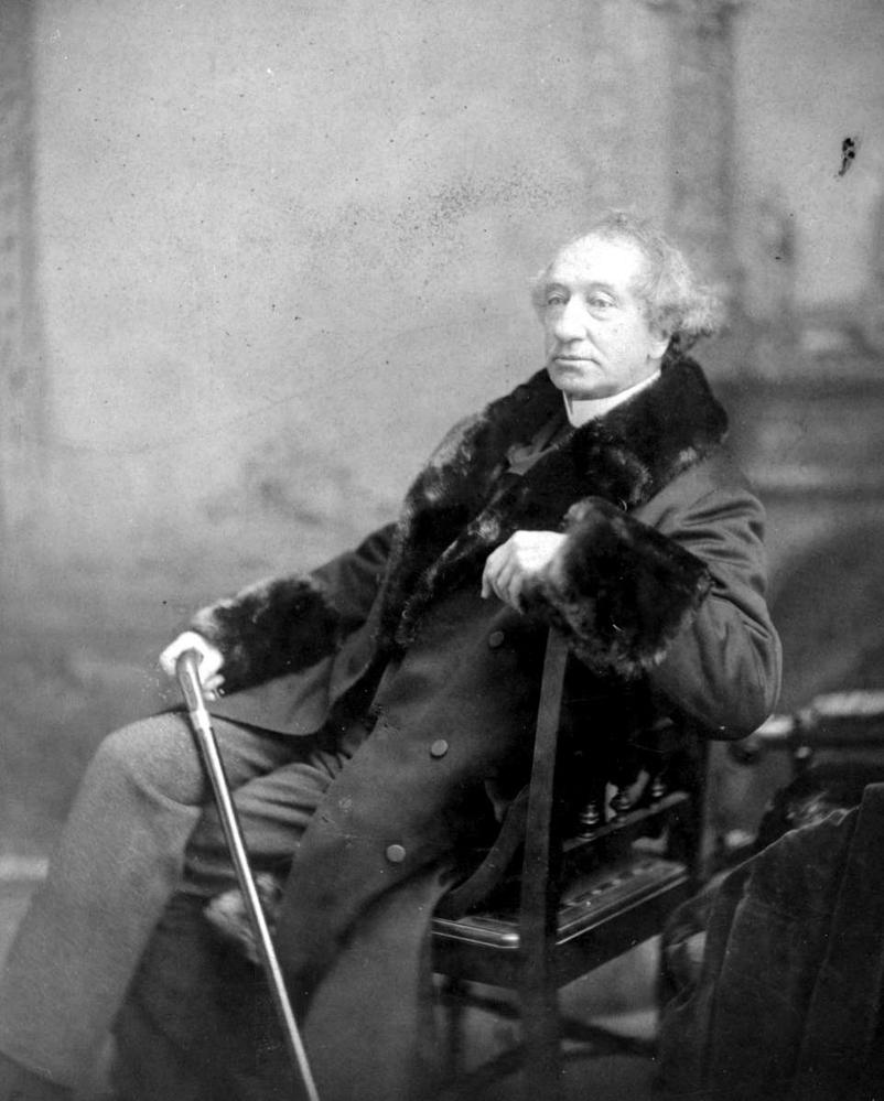 Man sat in chair in fur lined coat with cane.