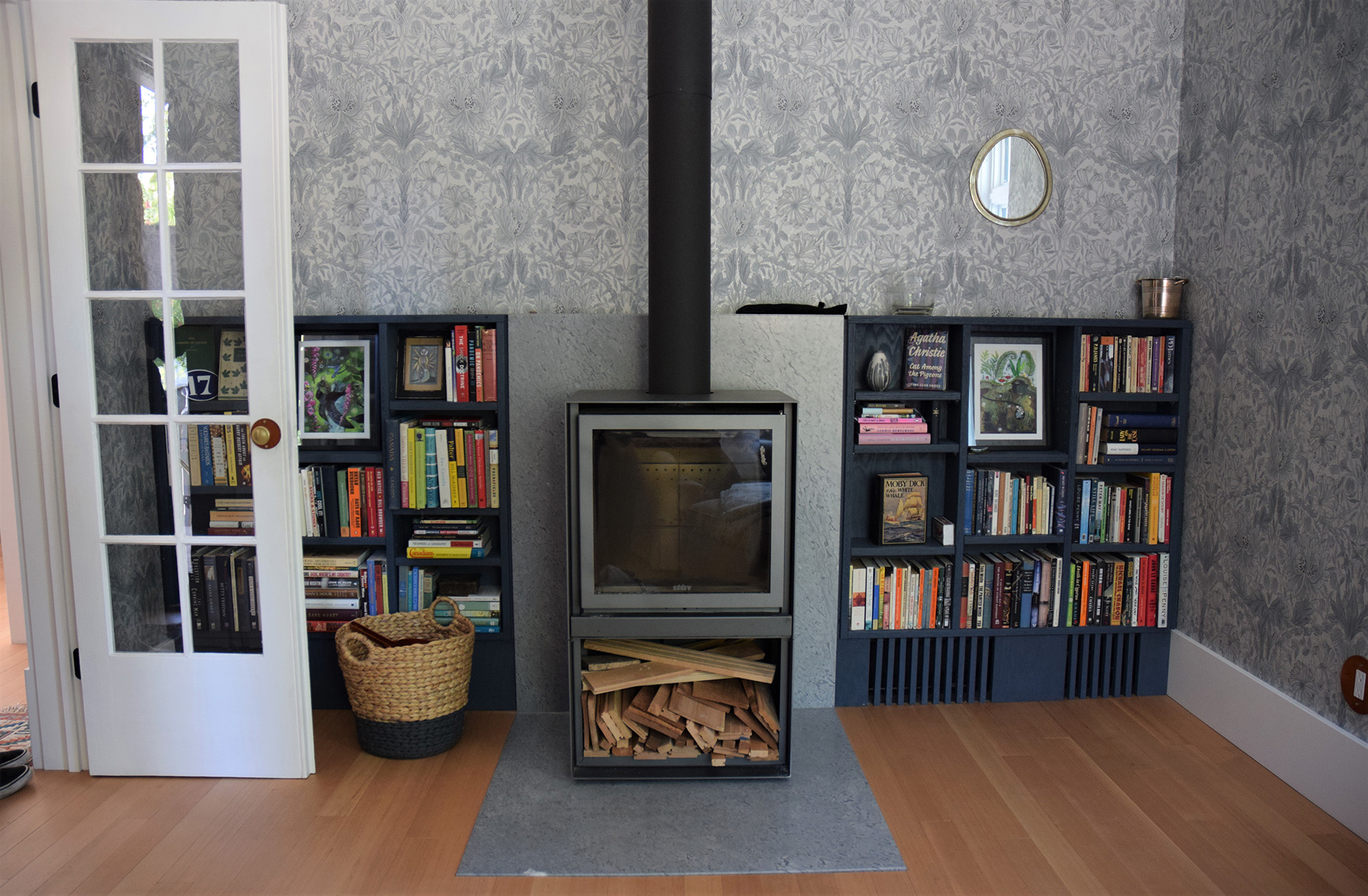 A living room with a wood-burning stove, bookshelves, and historic wallpaper.