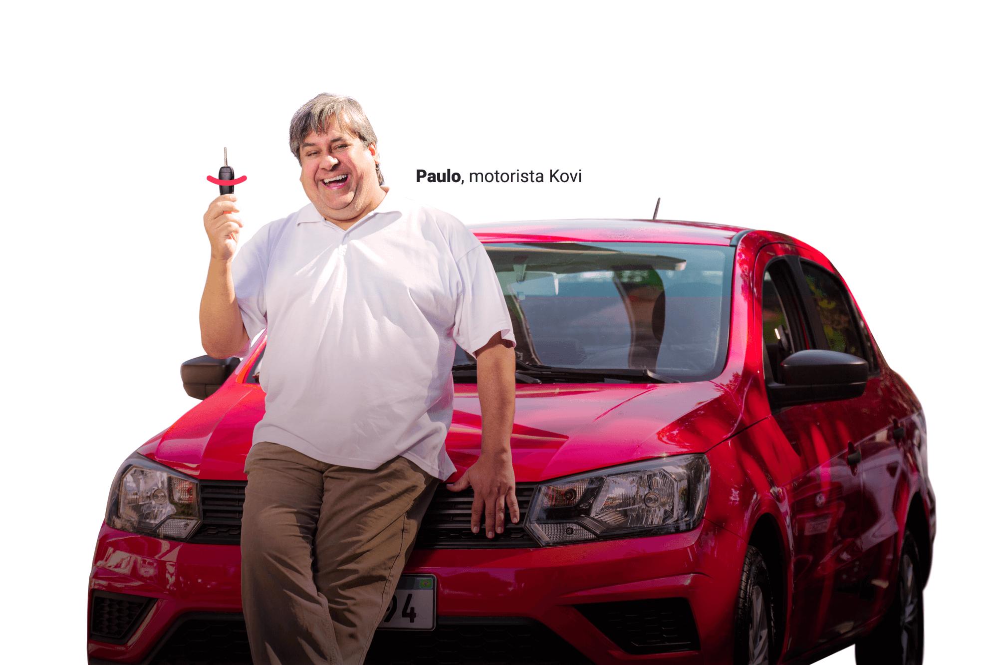 Foto do Paulo, motorista Kovi, sorrindo enquanto mostra a chave do carro no qual está sentado na frente.