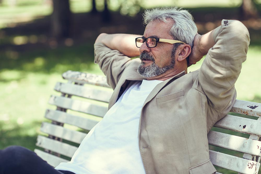 Older man sitting on a park bench with his arms behind his neck