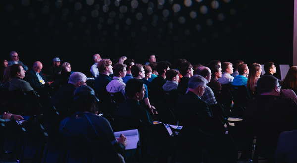 Several seated audience members at a presentation