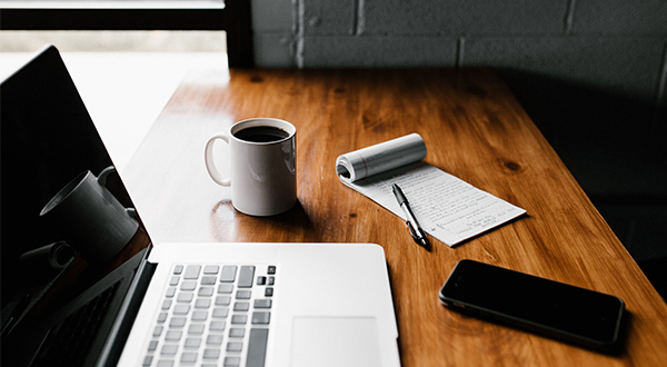 Laptop, coffee cup, cellphone, notepad and pen on a wooden desk