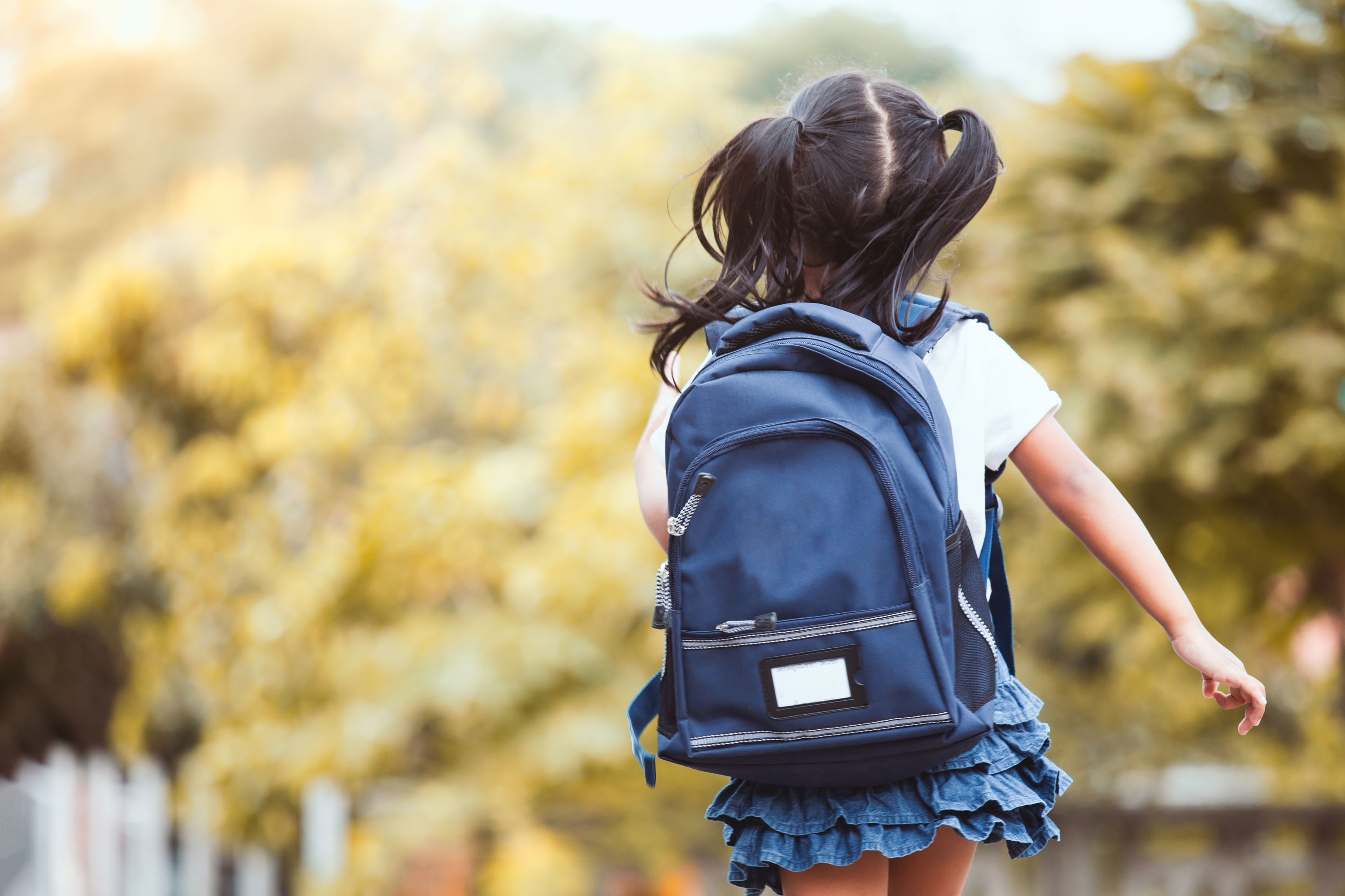 A child playing outside, wearing a navy backpack
