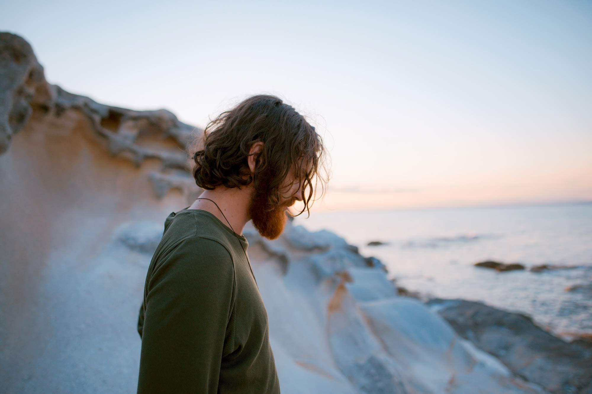 A man wearing a green shirt looks out at a coast of water