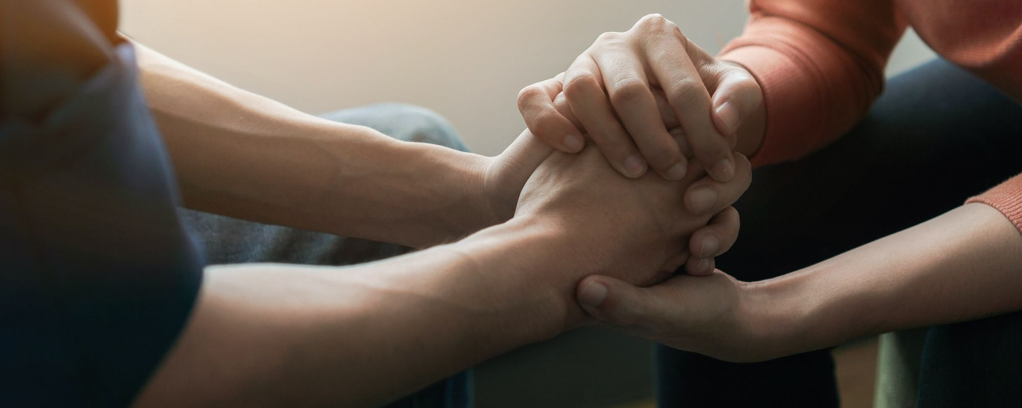 Giving up alcohol: A closeup of two people holding hands in support of each other