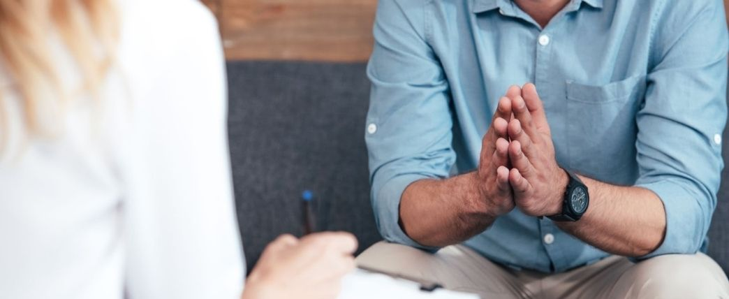 Living with OCD: A closeup of a man speaking to a therapist