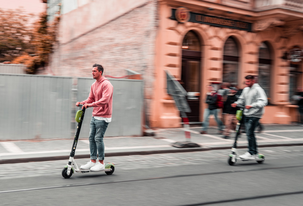 two men riding e-scooters on city street