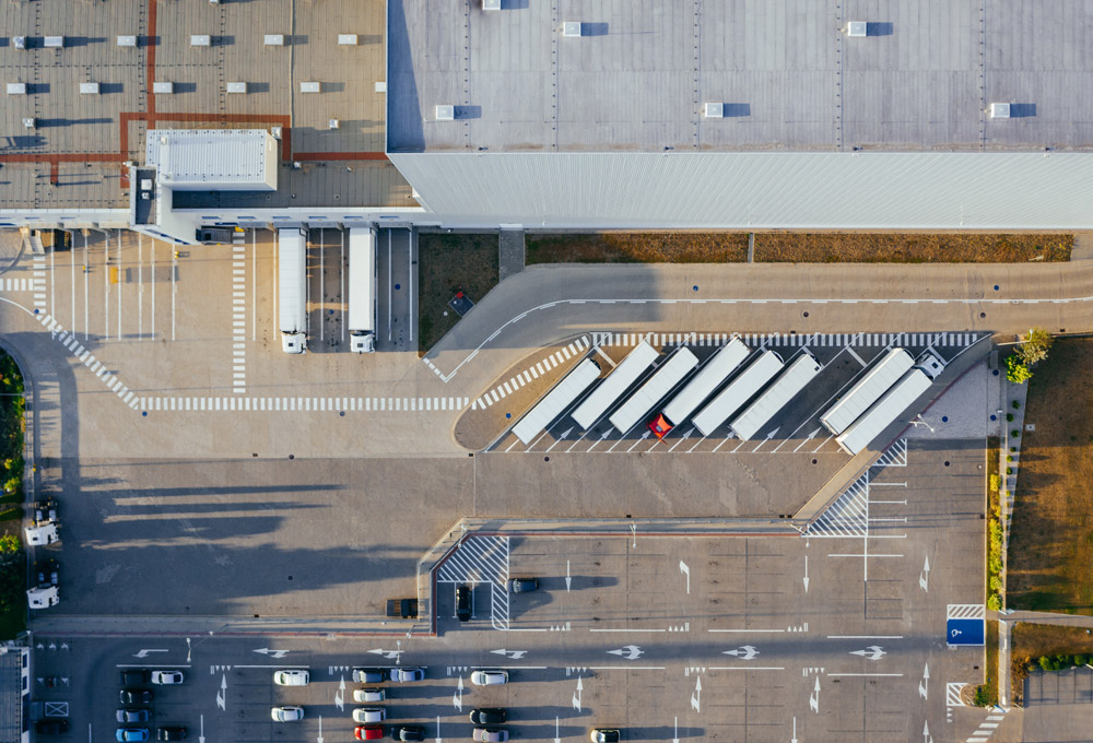 Aerial view of semi-trucks parked outside of a large warehouse