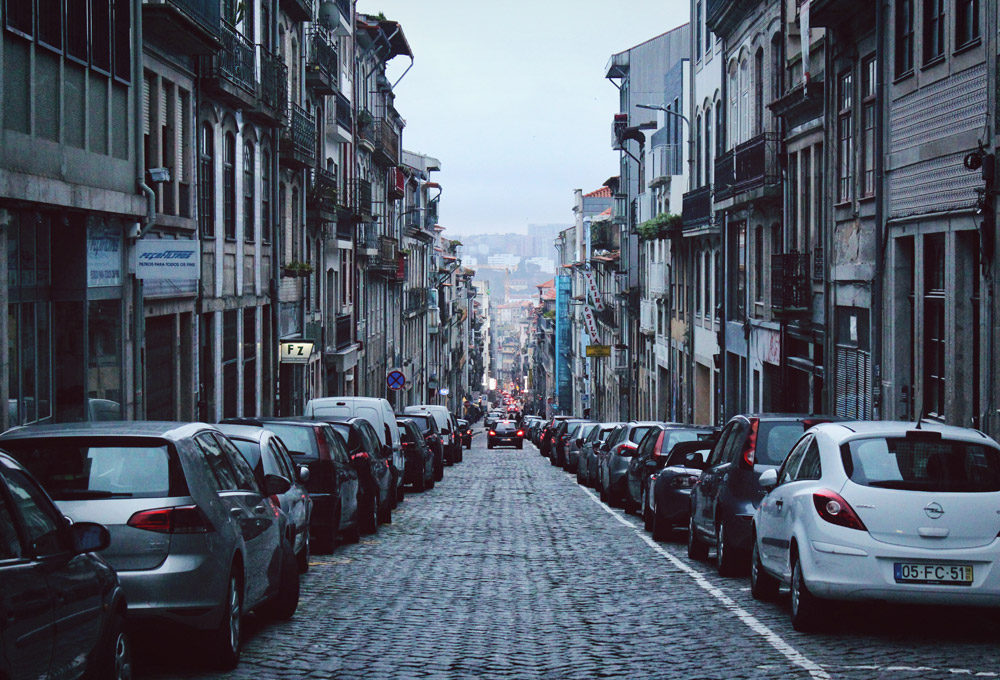 Narrow downhill road in Porto, Portugal with cars parked on both sides